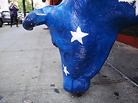 USA. New York City. A blue american cow sculpture outside a restaurant. A tourist takes a picture with a small digital camera. 25.10.2011 &copy; 2011 Didier Ruef