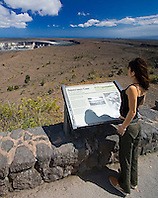 Woman visitor looking over Halema`uma`u Crater, Kilauea Caldera, Hawaii Volcanoes National Park, Big Island, Hawaii