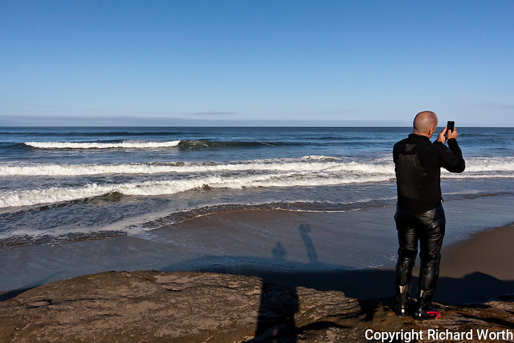An unidentified visitor to Pomponio State Beach on the California coast documents the waves, the sand, the ocean and shore with his phone.