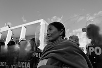 An Indian woman stands in front of the riot police block during the Inti Raymi (San Juan) festivities in Cotacachi, Ecuador, 24 June 2010. 'La toma de la Plaza' (Taking of the square) is an ancient ritual kept by Andean indigenous communities. From the early morning of the feast day, various groups of San Juan dancers from remote mountain villages dance in a slow trot towards the main square of Cotacachi. Reaching the plaza, Indians start to dance around. They pound in synchronized dance rhythm, shout loudly, whistle and wave whips, showing the strength and aggression. Dancers from either the upper communities (El Topo) or the lower communities (La Calera), joined in respective coalitions, seek to conquer and dominate the square and do not let their rivals enter. If not moderated by the police in time, the high tension between groups always ends up in violent clashes.