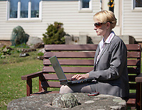Businesswoman Sitting and Working on Bench Using  Laptop Computer