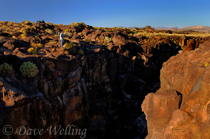 730850346 a hiker overlooks the  lava rocks and formations looking east from fossil falls blm protected lands inyo county california
