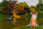 Old Westbury, New York, U.S. 22nd June 2013. Standing by the pond at dusk, MORGAN, 9, of East Islip, is one of many young girls wearing fairy costumes at the Midsummer Night event at Old Westbury Gardens, with dances performed throughout the illuminated grounds of the historic Long Island Gold Coast estate.