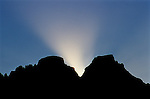 Sunset silhouette of the Horns, Ukhahlamba-Drakensberg Park, KwaZulu-Natal, South Africa. Crepuscular rays (God beams) diffracting at the neck between Inner Horn 3005m / 9858ft (left) and Outer Horn 3006m / 9860ft (right).  The saw-tooth profile of tiny peaks to the left is a group called the Chessmen.  Inner Horn was first climbed in 1925; Outer Horn in 1934.  The names are believed to have been derived from the Zulu name for nearby Cathedral Peak.  However, under some lighting conditions, as seen here, the gap between the Horns resembles antlers or deer horns.  One of the last free ranges of the San people or Bushmen, the Drakensberg is steeped in San folk lore.  Nikon F100, 70-300/4-5.6D, Kodak E100VS.