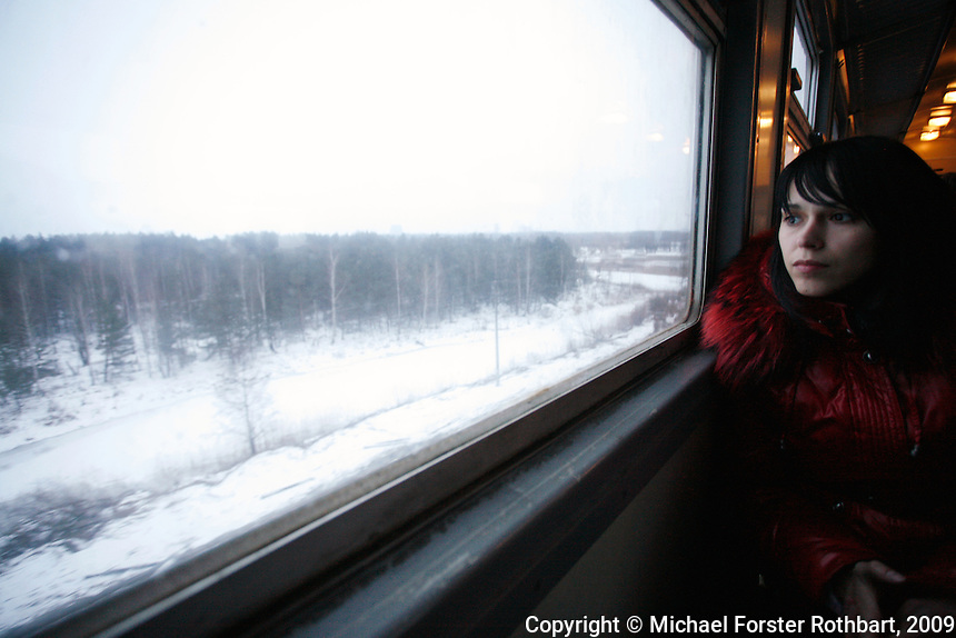On the train home, Tanya Bokova watches for moose and other wildlife. She was born in Pripyat and wanted to work at Chernobyl for as long as she can remember, like her grandfather and parents. Many workers meet their friends in the same section of the same train car during the hourlong ride each day.<br /> ------------------- <br /> This photograph is part the book of Would You Stay?, by Michael Forster Rothbart, published by TED Books in 2013. The photos come from Forster Rothbart&rsquo;s two long-term documentary photography projects, After Chernobyl and After Fukushima.<br /> &copy; Michael Forster Rothbart 2007-2013.<br /> www.afterchernobyl.com<br /> www.mfrphoto.com &bull; 607-267-4893 &bull; 607-436-2856<br /> 34 Spruce St, Oneonta, NY 13820<br /> 86 Three Mile Pond Rd, Vassalboro, ME 04989<br /> info@mfrphoto.com<br /> Photo by: Michael Forster Rothbart<br /> Date:  2/2009    File#:  Canon 5D digital camera frame 58112