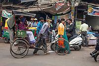 Agra, India.  Street Scene, Kinari Bazaar Area.  Walking a Rickshaw with Three Passengers.