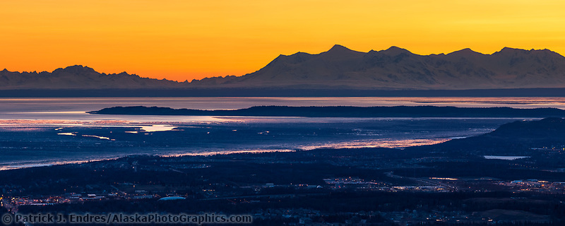 Sunset over the city of Anchorage situated along Cook Inlet with the Aleutian range mountains in the background.