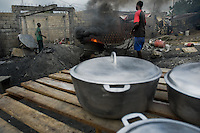 Haitian men work around the burning barrel in the aluminium recycling shop on the street of Port-au-Prince, Haiti, 11 July 2008.