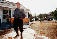 SJ02:FLOOD: SAINT JOHN, NEW BRUNSWICK: 10MAR98 - John Nutter (R) looks anxiously at the flood waters surrounding his house in Welsford, NB, while his wife Ada watches from dryer ground. 70 millimetres of rain in about 6 hours left most of the low-lying areas of Welsford flooded Tuesday morning.&amp;#xD;<br />