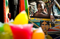 A Haitian girl looks out of the window of the tap-tap bus in the downtown of Port-au-Prince, Haiti, 25 July 2008. Tap-tap vehicles serve as public transportation in Haiti. They are private, operate over fixed routes, departing only when full. Tap-taps are decorated with bright and shiny colors and with a lot of fancy designed elements. There are scenes from the Bible, Christian slogans, TV stars or famous football players often painted on a tap-tap body. Tap-tap name comes from sound of taps on the metal bus body signifying a passenger's request to be dropped off.