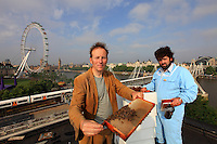 The hives of the Royal Festival Hall. Barnaby Shaw and Mikey Tomkins posing in front of a hive at the Royal Festival Hall, with the Parliament buildings and the Thames in the background.