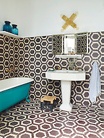 A striking bathroom has a vintage sink tiles by Popham Design's Hex Zig Zag. A blue free-standing roll top bath stands against one wall.