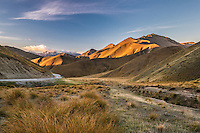 Lindis Pass highway weaves through rolling hills at sunset in Central Otago, New Zealand