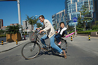 A father-son commuter on the bike lanes near Olympic Stadium. Beijing has dedicated bicycle land infrastructure throughout many areas of the city.