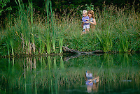 Mother teaching daughter to fish amidst tall grass on shore of lake