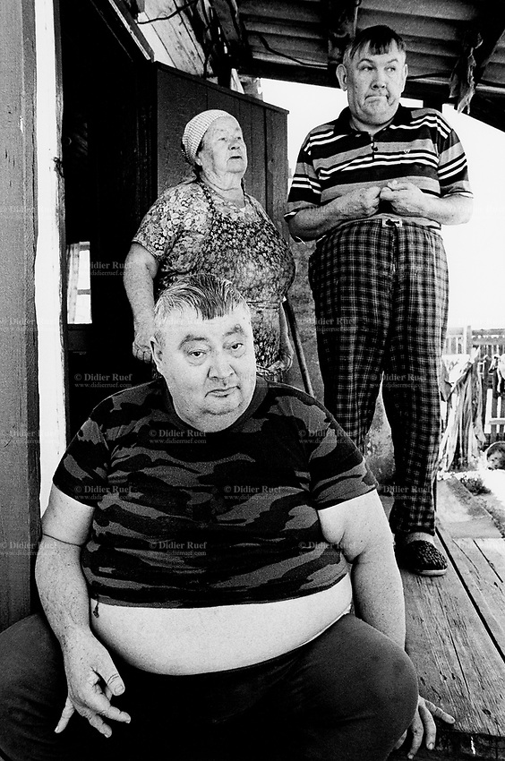 Kazakhstan. Dolon. Ludmila Shakhvorostova (77 years old) is the mother of Alexander Shakhvorostov (fat man seated, born 1958) and Anatoliy Shakhvorostov (stand up, born 1956). Both sons are mentally handicapped. They both suffer from mental deficiency and retardation. The village of Dolon is near the Semipalatinsk Polygon ( called today National Nuclear Center of Kazakhstan). Both sons are second generation victim of the 456 atomic testing - 116 atmospheric, 340 underground - from 1949 to 1989. Ludmila Shakhvorostova still remembers seing the first atom test in 1949. The regions high frequency of mentally handicapped diseases is primarily due to fallout from nearby nuclear test sites. Both men show the human and environmental effects of nuclear radiation, genetic contamination and pollution from atomic tests programs of the former Soviet Union. Dolon is located in the Eastern Kazakhstan Province. © 2008 Didier Ruef ..