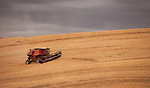 This combine works a large wheat field under the hot sun during the month of August in the Palouse of Eastern Washington.