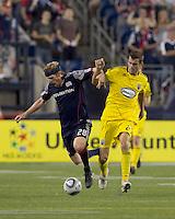 New England Revolution midfielder Pat Phelan (28) and Columbus Crew defender Eric Brunner (23) collide. The New England Revolution tied Columbus Crew, 2-2, at Gillette Stadium on September 25, 2010.