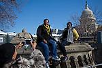 Tourists pose for pictures in front of the Capitol the day before the presidential inauguration, January 20, 2013 in Washington, D.C.