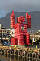 "South Africa, Cape Town. ""Lego Man"" sculpture made of 4200 plastic  Coca Cola crates.  Designed by Porky Hefer.  Victoria & Alfred Waterfront.  Table Mountain in background."