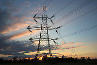 Two forms of energy - setting sun behind electricity pylon and power cables in landscape at sunset in England, UK
