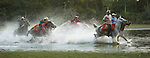 Cowboys or vaqueros splash through water on their horses.