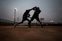 Peruvian youths practice boxing sparring during the dusk at the Boxeo VMT boxing club in an outdoor gym in Lima, Peru, 3 July 2013. Boxeo VMT is a grassroots organisation offering boxing lessons to youth as an alternative to gang violence, crime and drug-trafficking. Located in some of Lima's most marginalized neighborhoods, Boxeo VMT club joins nearly 50 young men. Although the club disposes only of an unequipped outdoor facility with couple of punching bags, the young boxers train hard three times a week and dream to become a boxing champion.