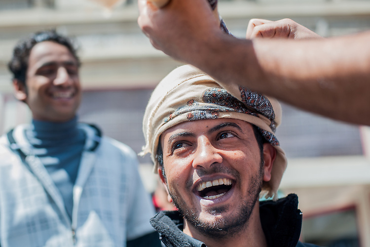 Manasar Alharethi laughs as Rashid Alsaadi wraps his head with cloth to create an omani mussar at the international street fair. Photo by: Ross Brinkerhoff.