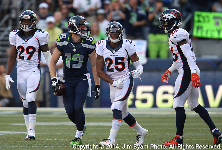 Seattle Seahawks  wide receiver Bryan Walters (19)  gets up and looks over at  Denver Broncos cornerback Bradley Roby (29), Chris Harris Jr., and Rahim Moore (26) after  catching a pass for an 11-yard gain in the fourth quarter at CenturyLink Field in Seattle, Washington on September 21, 2014. The Seahawks won 26-20 in overtime