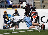 Chris Boland (32) of Johns Hopkins is fouled by Chris Chandler (16) of Princeton during the Face-Off Classic in at M&T Stadium in Baltimore, MD