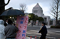 March 11, 2012, Tokyo, Japan - A crowd of demonstrators gathers in the cold and rain outside the building Kokkai-Gijido or The National Diet of Japan. Many protesters carrying banners took to the streets of Tokyo to demonstrate against nuclear power on the first anniversary of the Great East Japan Earthquake. (Photo by Rodrigo Reyes Marin/AFLO) (JAPAN)