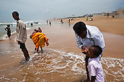 A young man is seen feeding sea water to his young child on the shores of Puri Beach along the Bay of Bengal in Puri, Orissa, India. A dip in its salty waters is believed to hold great religious significance, as a result these golden sand beaches sees is a never-ending rush of pilgrims and tourists. Photo: Sanjit Das/Panos