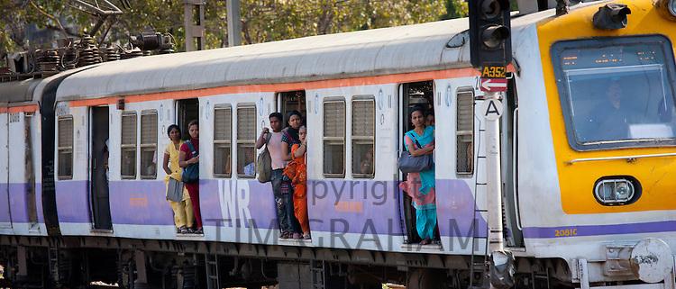 Female workers on crowded commuter train of Western Railway near Mahalaxmi Station on the Mumbai Suburban Railway, India