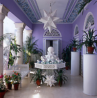 Three sets of double doors open on to the veranda with its collection of potted palms and succulents