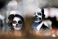 A young couple, costumed as 'La Catrina', a Mexican pop culture icon representing the Death, walks through the town during the Day of the Dead celebration in Morelia, Michoacán, Mexico, 1 November 2014. Day of the Dead ('Día de Muertos') is a syncretic religious holiday, celebrated throughout Mexico, combining the death veneration rituals of the ancient Aztec culture with the Catholic practice. Based on the belief that the souls of the departed may come back to this world on that day, people gather on the gravesites praying, drinking and playing music, to joyfully remember friends or family members who have died and to support their souls on the spiritual journey.