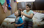 Four-year old Bahar Nawar protests as Hanen Yousif brushes her hair in the basement of Sacred Heart Catholic church in Amman, Jordan, where 60 Iraqi Christian refugees are living. The Lutheran World Federation, a member of the ACT Alliance, has helped the church feed the refugees and remodel the basement into partitioned areas to provide some privacy for the ten refugee families.<br /> <br /> Parental consent obtained.