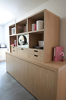A kitchen unit and open shelving are both made of oak