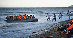 Refugees land on a beach near Molyvos, on the Greek island of Lesbos, on October 31, 2015, after crossing the Aegean Sea from Turkey. Local and international volunteers welcome the arriving refugees with food and medical care and dry clothes before they proceed on their way toward western Europe. Their boat to Greece was provided by Turkish traffickers to whom the refugees paid huge sums to arrive in Greece.