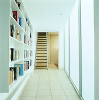 The gallery links the original house with the extension with opalescent glass forming one wall and a bookcase the other