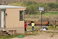 Kids play basketball outside a trainler home as a loaded coal train passes on the Crow Reservation at Crow Agency, Montana, Thursday, May 16, 2013. Pending new ports for shipment to Asia through either the U.S. or Canada, Cloud Peak Energey hopes to open new high-grade coal mines on and near the Crow Reservation in southern Montana. The tribe is equally hopeful the new mines would bring long-awaited economic stability to the tribe. (Kevin Moloney for the New York Times)