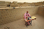 Ali Ould Bruye is a tailor who fled Timbuktu, a city in northern Mali, when it was seized by Islamist fighters in 2012. He and his family returned home in May, 2013, after the city and region had been liberated by French and Malian soldiers. Here he works on the roof of his house in Timbuktu.