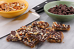 Ingredients needed to make pecan toffee lay on a marble cutting board with a chef's knife.
