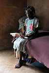 """Mislanda Ridore, 13, here reading her school work in her home, is a Peace Pal in the southern Haitian village of Mizak. Peace Pals is a program of the World Peace Prayer Society, which promotes the message """"May Peace Prevail on Earth"""" as a simple, universal expression to unite the hearts of all people in a common desire and hope for peace on Earth. Peace Pals provides a safe and nurturing environment for children to gather to play and learn lessons that organizers hope will lead to generational changes in attitudes about self-worth, care for the environment, personal health & hygiene, conflict resolution, respect for all persons and encouragement to be """"peacebuilders"""" at all levels. In Mizak, Peace Pals is sponsored by Haitian Artisans for Peace International (HAPI)."""
