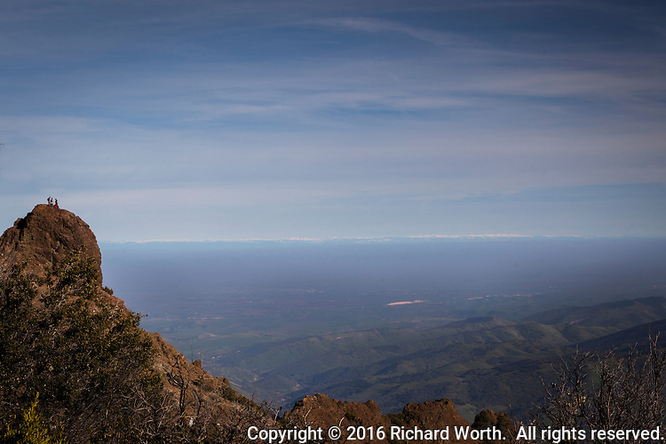 Three adventurous hikers stand on an outcrop near the Mount Diablo summit.  Across the horizon, the snow covered Sierra Nevada Mountains draw a jagged white line between the pale blue, cloud-streaked sky above and the rolling, green, haze-veiled hills below.