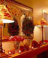 A miniature conifer tree decorated with a simple red ribbon is the centrepiece on this Christmas themed mantelpiece