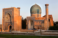 General view of monumental arch and Gur-Emir Mausoleum, 1417-20, Samarkand, Uzbekistan, pictured on July 14, 2010, in the warm light of sunset. Gur-Emir Mausoleum, or Tomb of the Ruler, was built by Timur in 1404 for his favourite grandson, Mohammed Sultan, and became the mausoleum for the Timurid dynasty. The simply formed building is an octagonal drum beneath an azure fluted dome (diameter: 15m, height: 12.5m). Its walls are tiled in blue and white geometric and epigraphic patterns including the words 'God is Immortal' in 3m. high white Kufic script around the top of the drum. Samarkand, a city on the Silk Road, founded as Afrosiab in the 7th century BC, is a meeting point for the world's cultures. Its most important development was in the Timurid period, 14th to 15th centuries. Picture by Manuel Cohen.