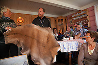 Deer farm in Norway. Owner Signy Torsvoll and Tim Röhlcke from Ecotrip are showing a deer hide to tourists from Switzerland.