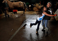 """Nahe Tachera, 9, and sister, Kamehana, 11, dance in the Kahua Ranch barn while their father, Wayne, shoes a horse in North Kohala, Hawaii.  The girls' great-grandfather, grandfather and father are or were all cowboys and they live in """"cowboy housing"""" on the ranch because their father is employed as one of the ranch's cowboys.  The girls learned to ride horses as toddlers and have grown up with the ranch as their playground. """"My dad's work is great.  While he works, we can play around the ranch and he doesn't have to worry about us"""", says Nahe."""