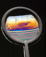 IRIDESCENCE: INTERFERENCE IN THIN FILM (SOAP)<br /> Light Interference Causes A Colorful Pattern<br /> Light reflected from one surface of wedge shaped soap film may cancel light that reflects from the other. If hit w/white light, complementary color results from destructive interference. As film thins, phase difference increases &amp; film appears black.
