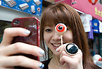 A woman takes her own photo holding a confectionary item modeled on a character in Gegege no Kitaro by Shigeru Mizuki on a street named after the manga artist in his home town of Sakaiminato, Tottori Prefecture, Japan..Photographer: Robert Gilhooly